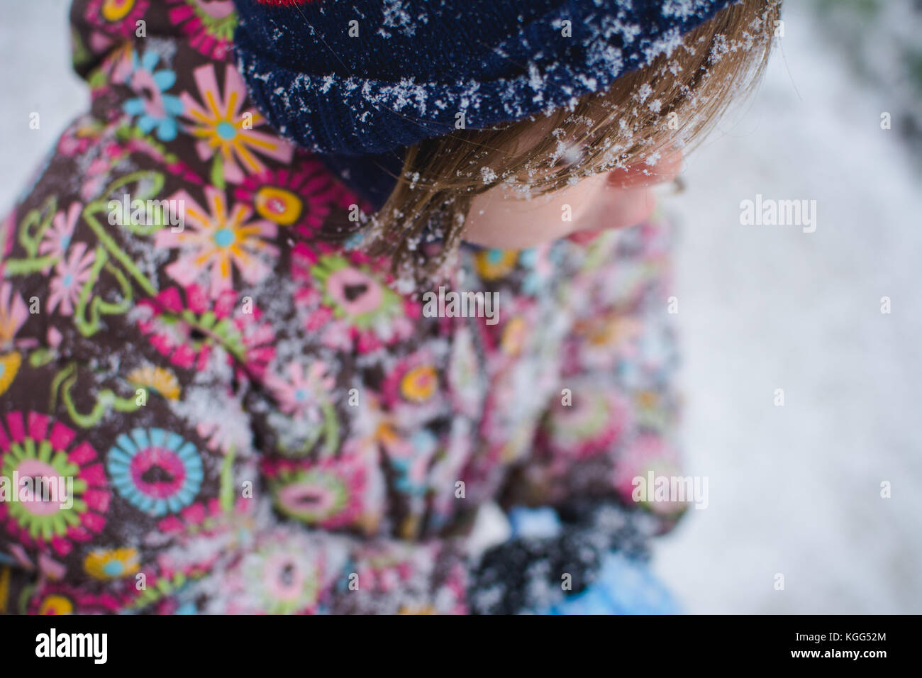 A toddler stands outside wearing winter clothes with snow around her. - Stock Image