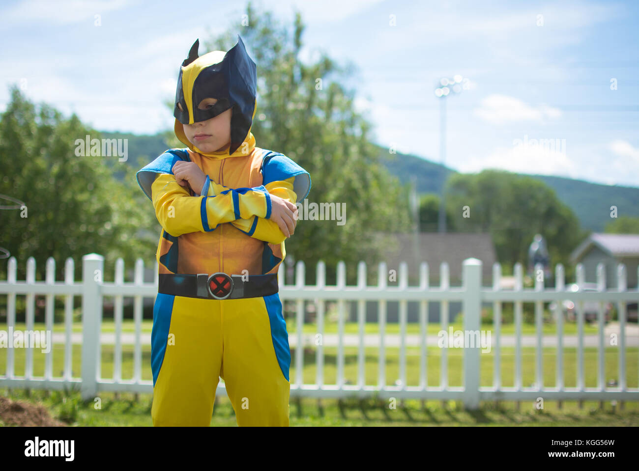 A young boy wears a costume standing outside with folded arms - Stock Image