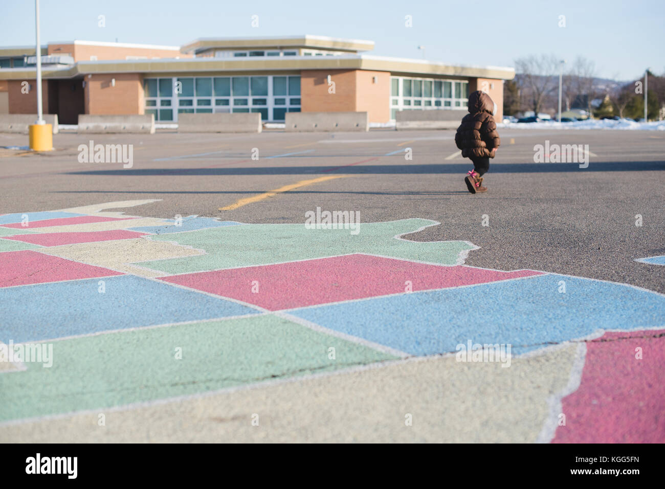 a young girl walks across the parking lot of a school - Stock Image