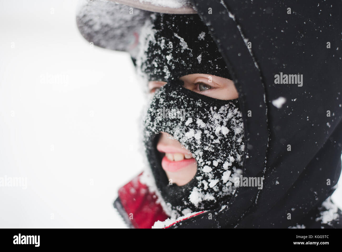 Child wearing a ski mask covered in snow - Stock Image