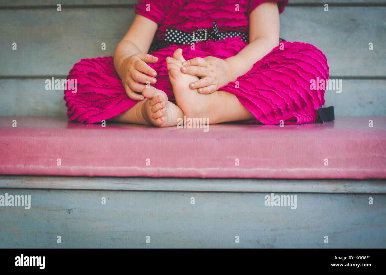 2-3 year old sitting on a bench with her bare feet visible. - Stock Image