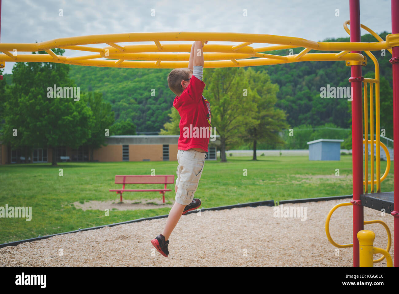 11-12 year old on climbing bars at a playground - Stock Image