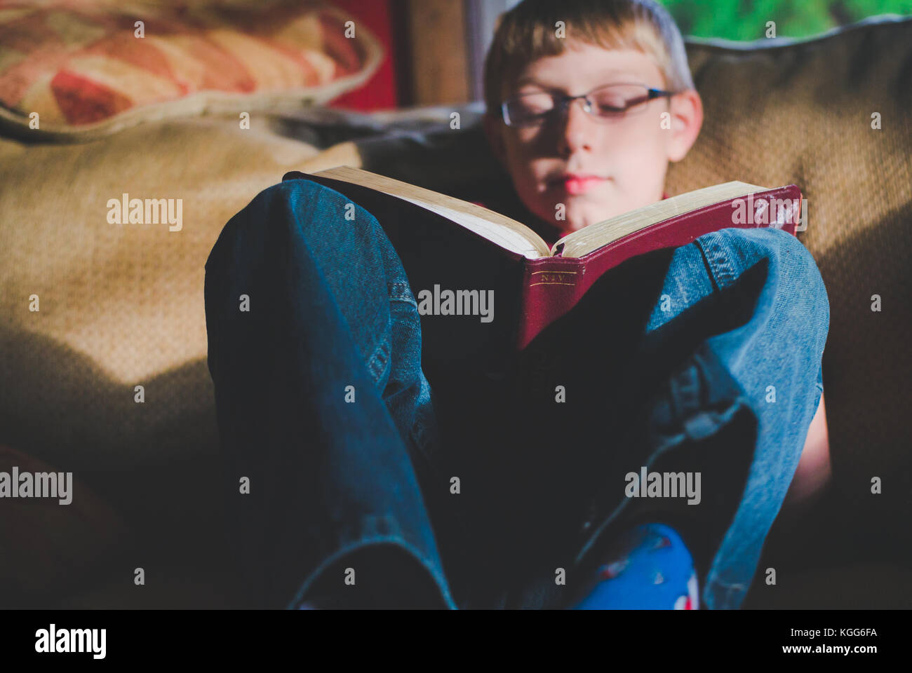 10-11 year old boy reading a book - Stock Image