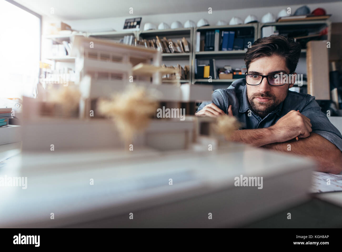 Young architect working on house model.  Male designer at his workdesk thinking about new architectural ideas. - Stock Image