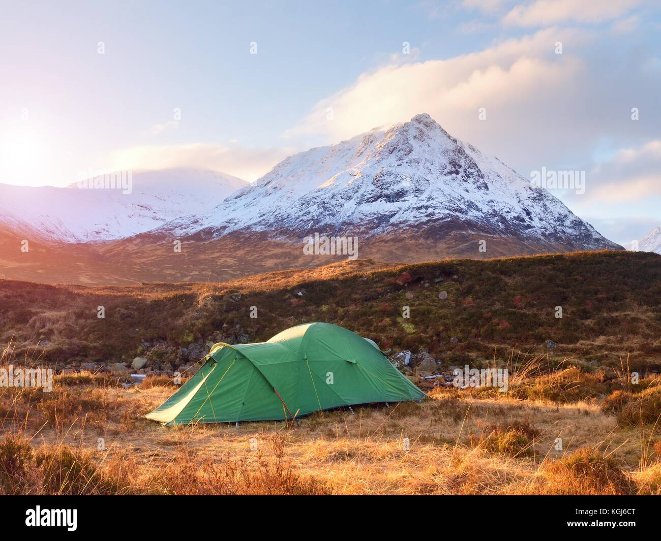 Green touristic tent on meadow at river below snowy cone of mountain Stob Dearg 1021 metres high. Higland in Scotland - Stock Image