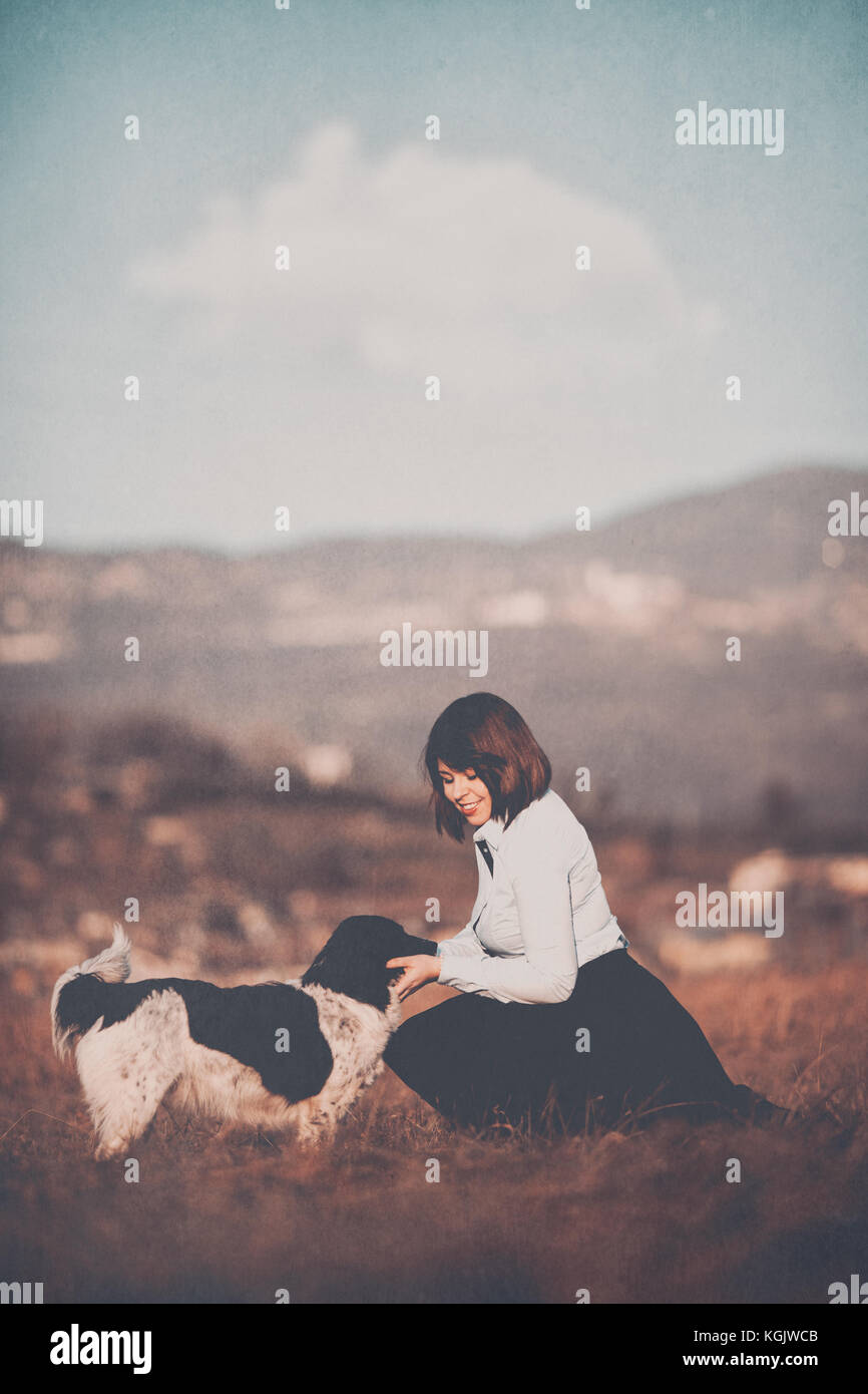 Girl sitting in a field, playing with a dog - Stock Image