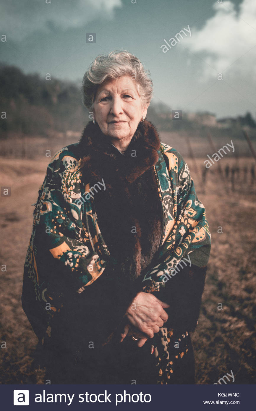 Old woman standing in a field in the countryside - Stock Image