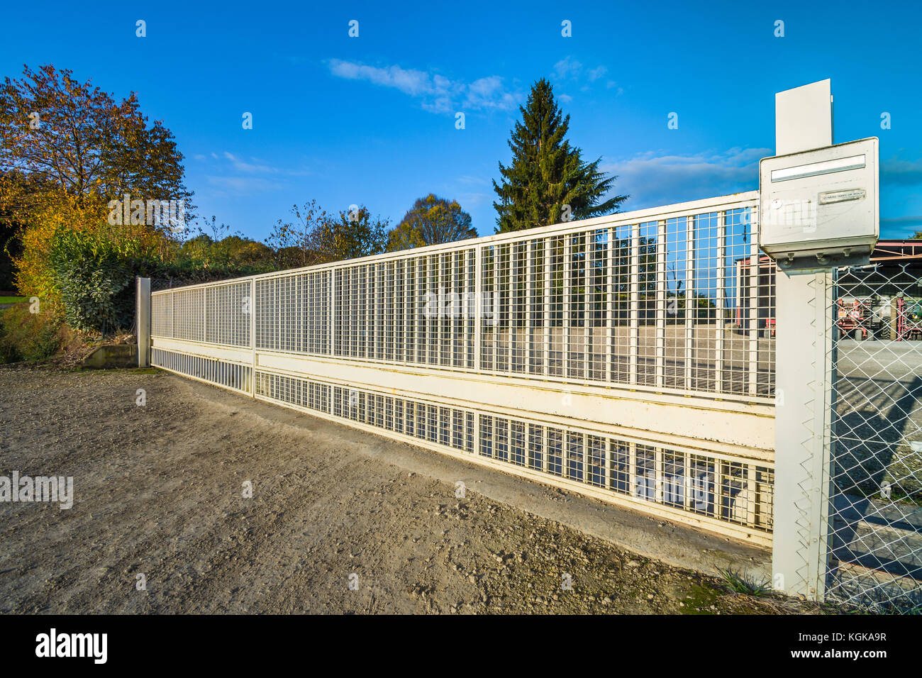 Long, sliding metal farm gate - France. - Stock Image