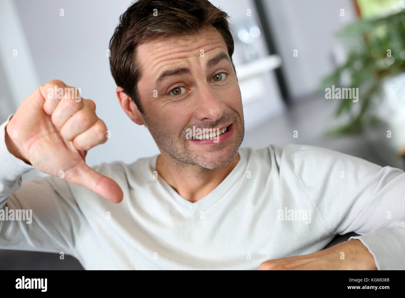 Discontented man showing thumb down - Stock Image