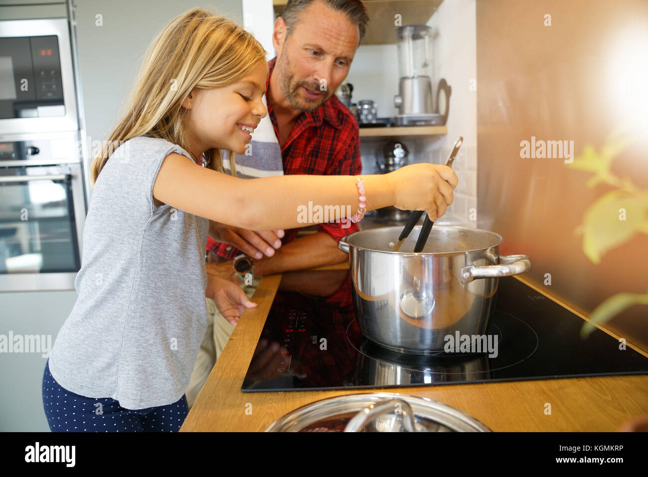 Daddy with daughter cooking together in home kitchen - Stock Image