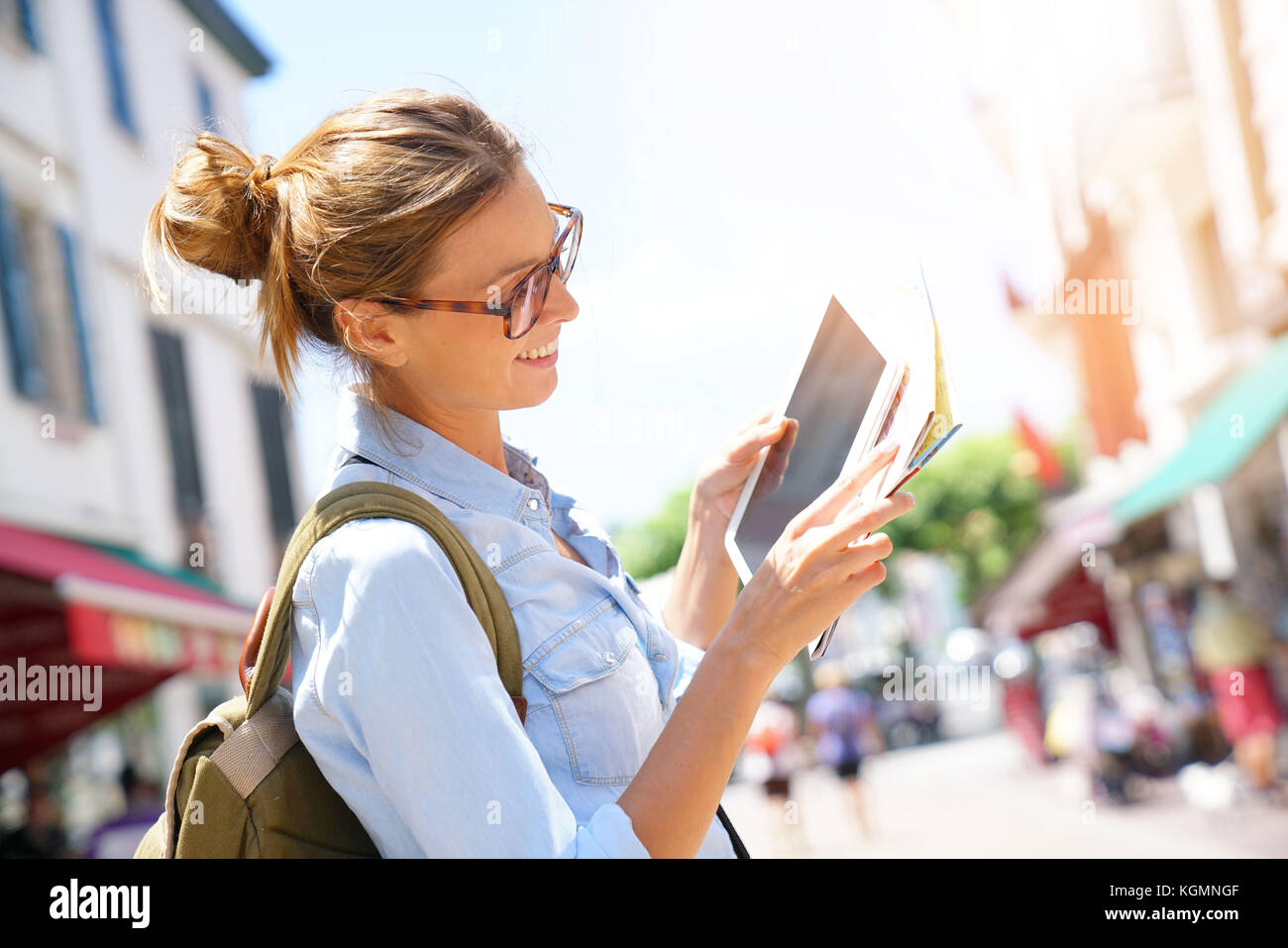 Happy tourist girl reading map and using tablet in the street - Stock Image