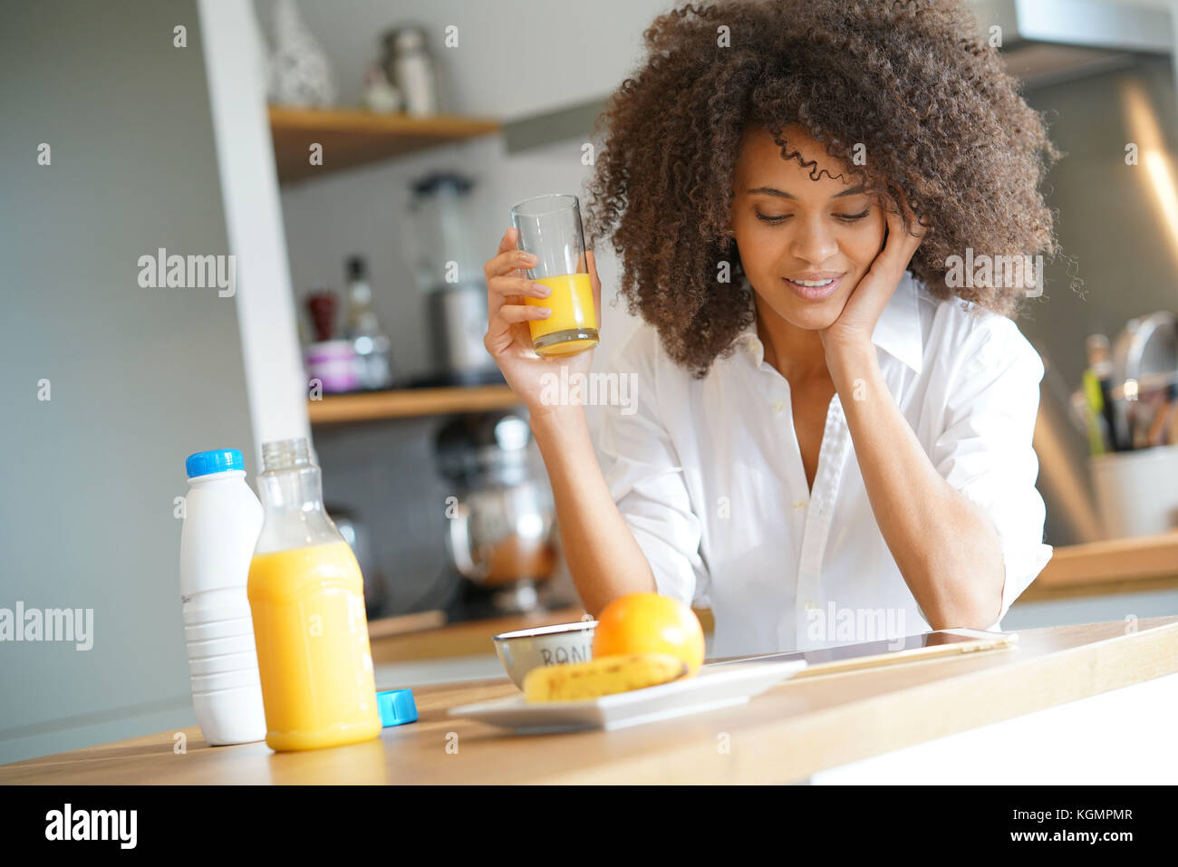 Mixed race woman sitting in kitchen having breakfast - Stock Image