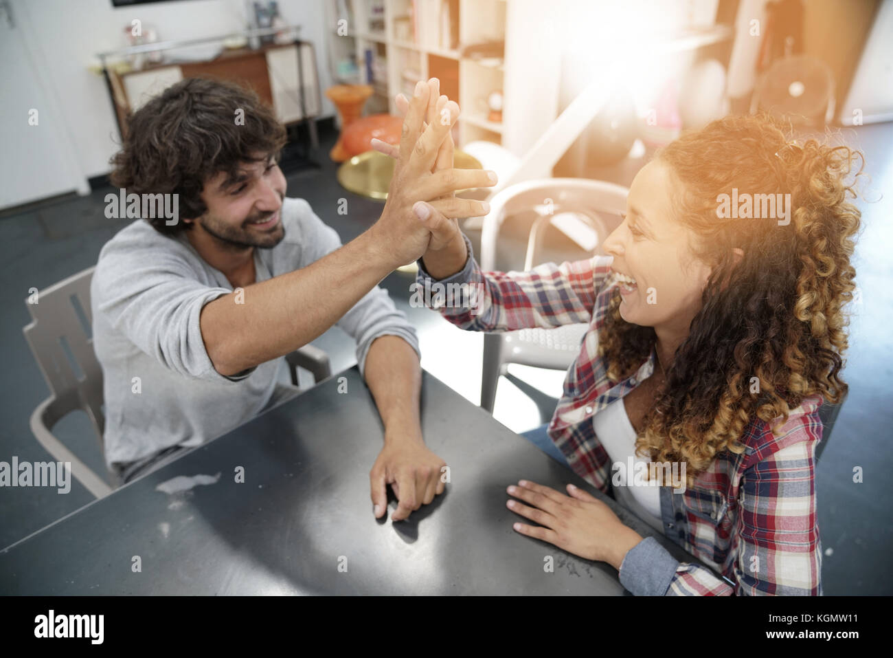 Co-workers  giving one another high five - Stock Image