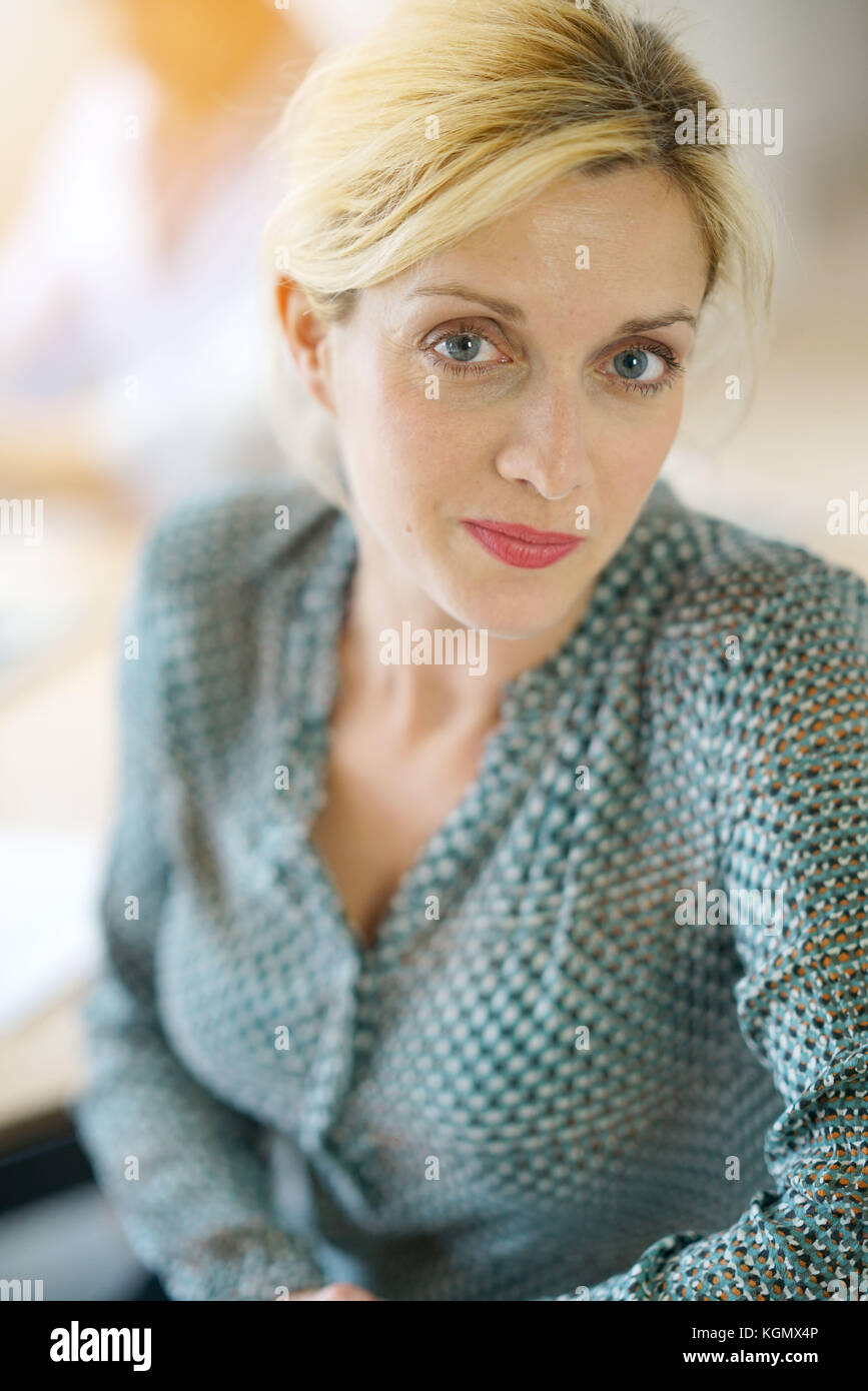 Portrait of 40-year-old blond woman with blue eyes - Stock Image