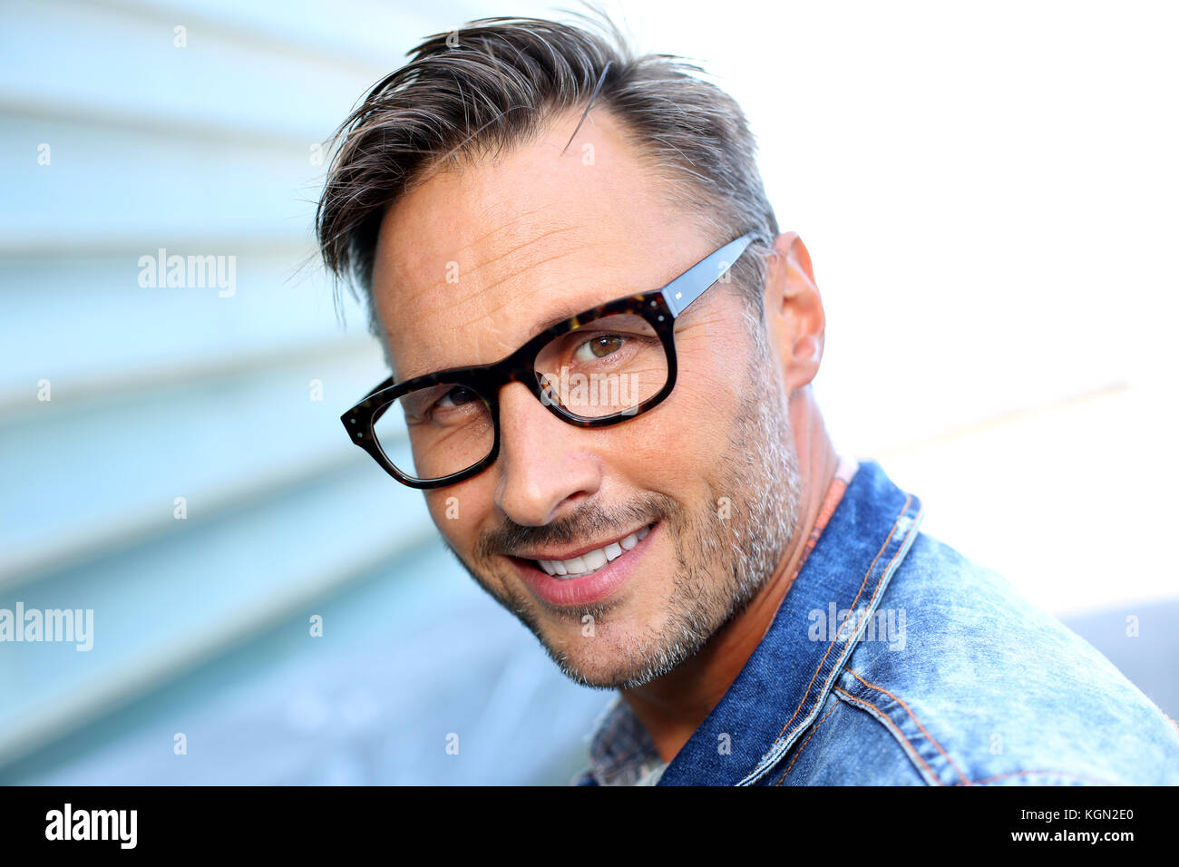 dd4afc805eb Smiling man wearing eyeglasses and blue jeans jacket Stock Photo ...