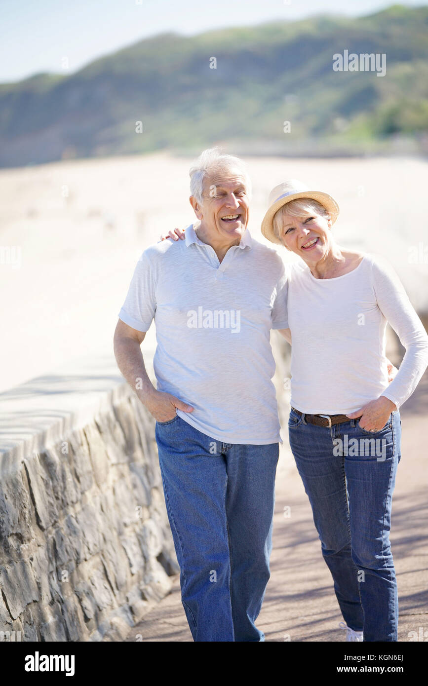 Senior couple walking by the beach, spring time - Stock Image