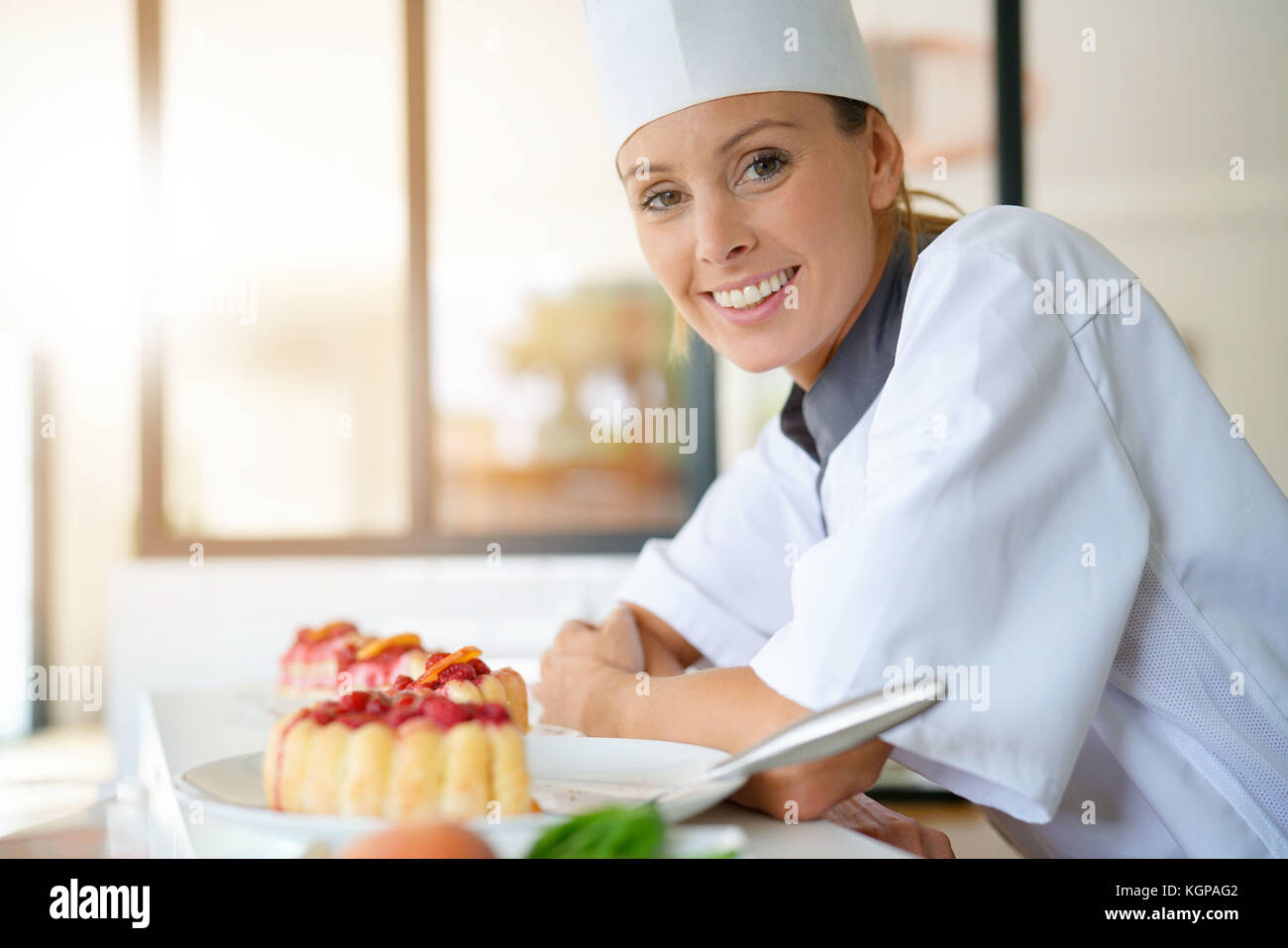 Smiling pastry chef standing in restaurant kitchen - Stock Image