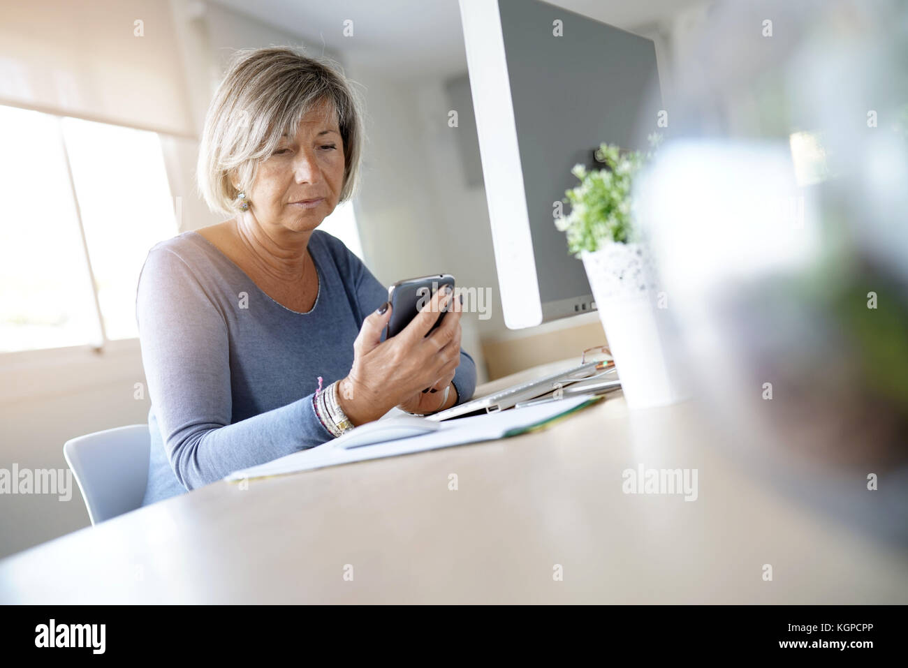 Senior woman working in office using smartphone - Stock Image