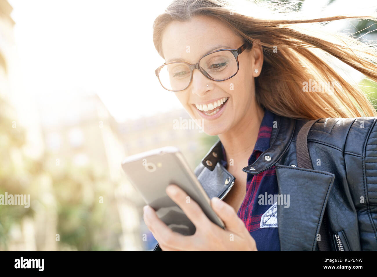 Portrait of trendy girl in town using smartphone - Stock Image