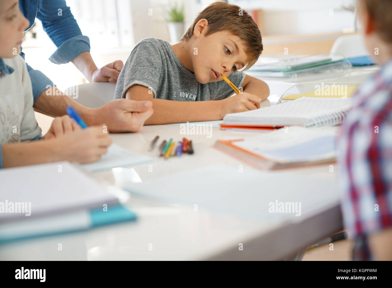 Kids writing notes in classroom - Stock Image