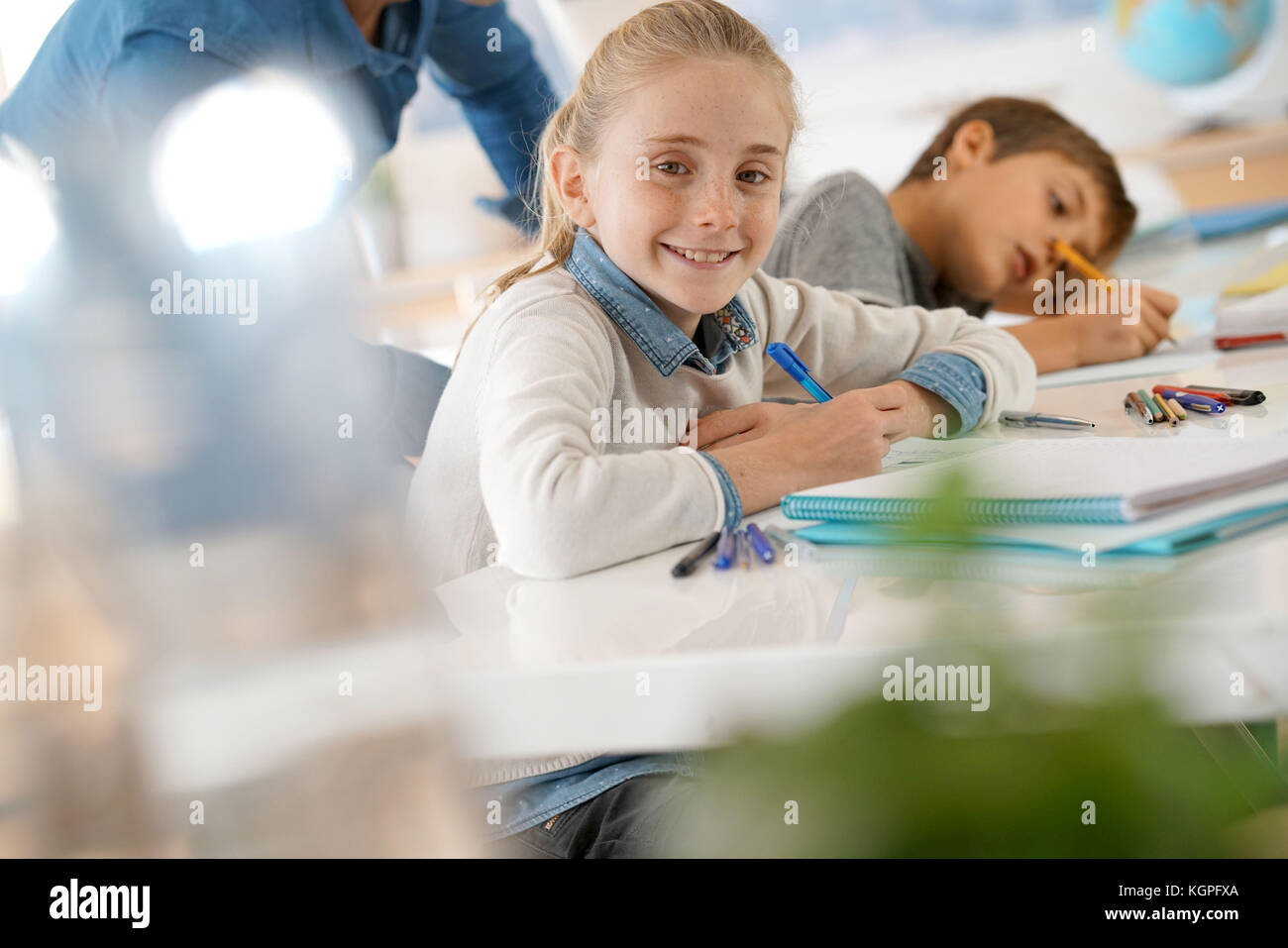 Portrait of school girl taking notes in class - Stock Image