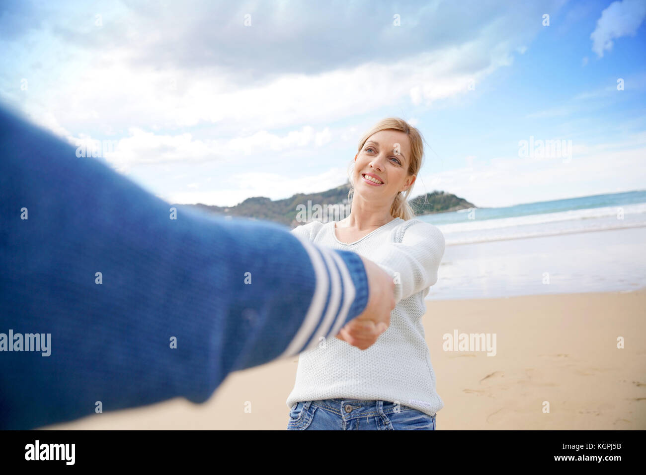 Middle-aged couple on the beach having fun turning around - Stock Image