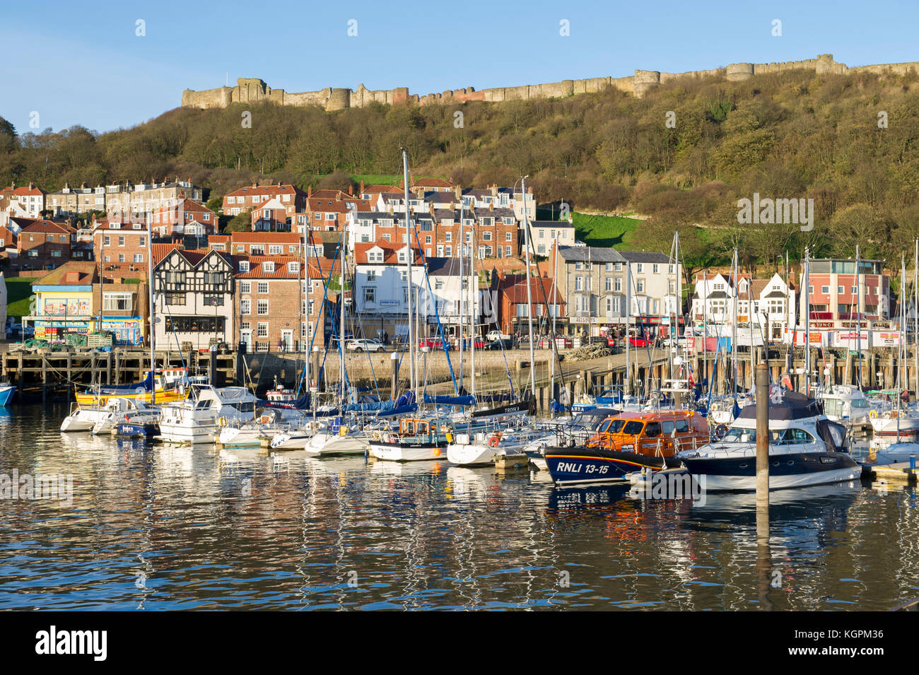 The boats in the Harbour overlooked by the buildings and the historic Castle in the North Yorkshire seaside town - Stock Image