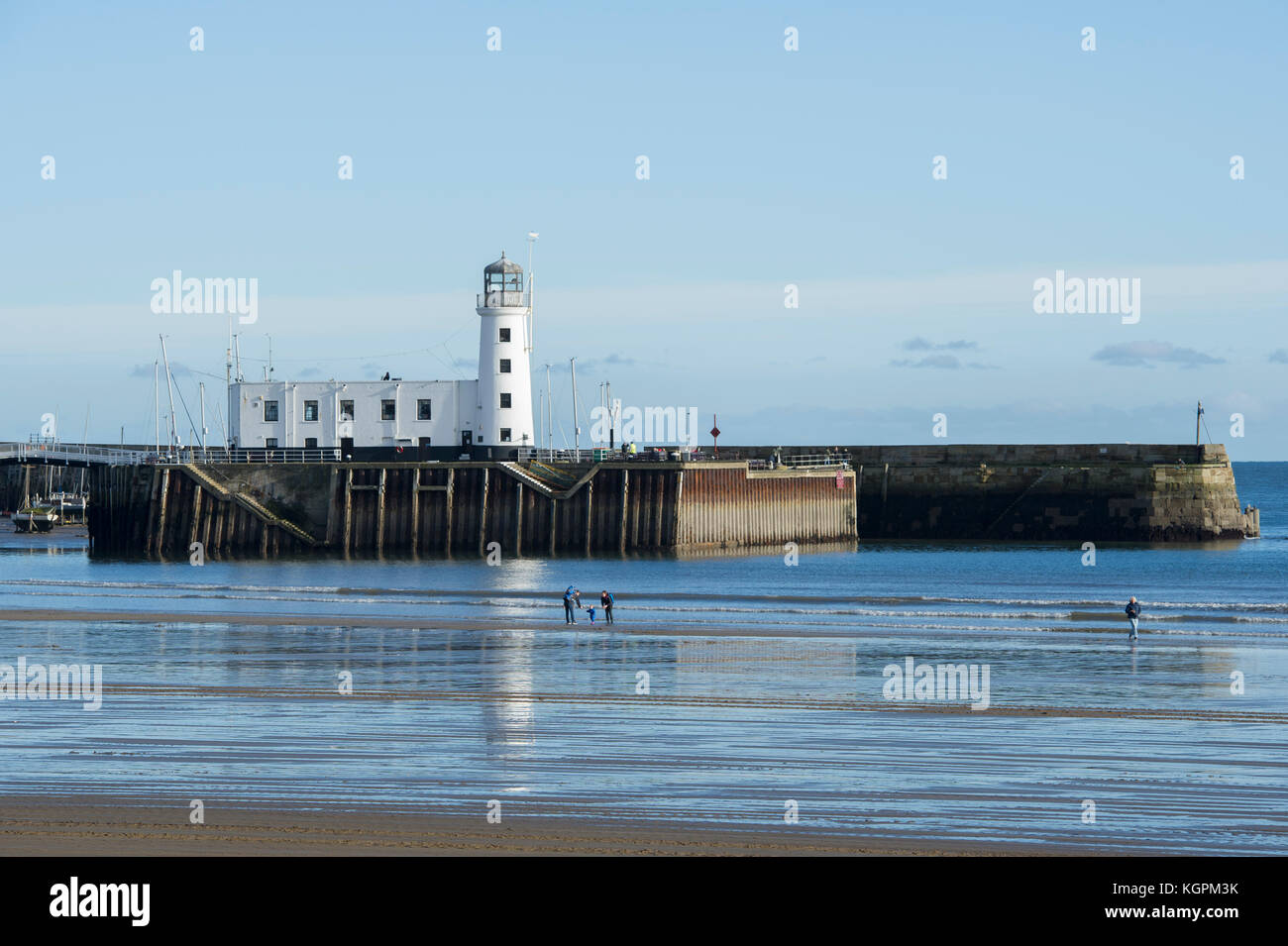 Scarborough Harbour and Lighthouse on a sunny Autumn afternoon with tourists walking on the beach of the North Yorkshire - Stock Image