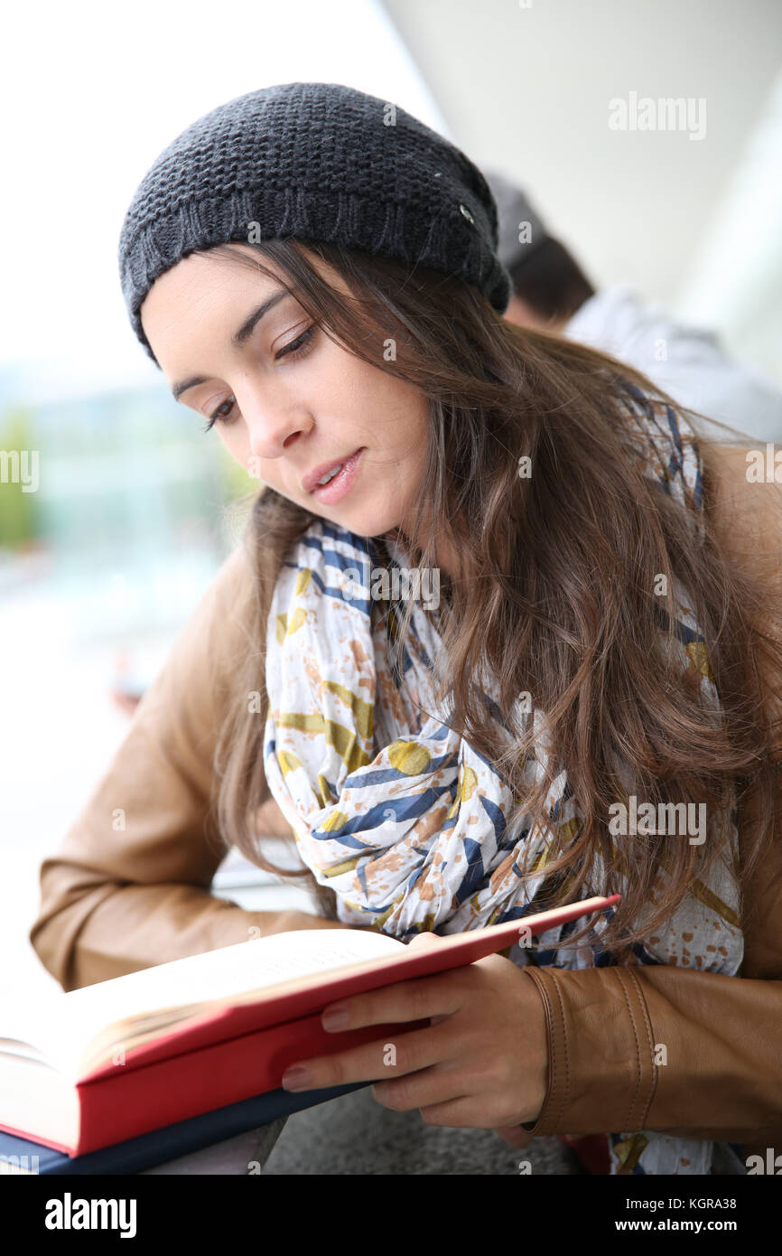 Student girl reading book outside school building - Stock Image