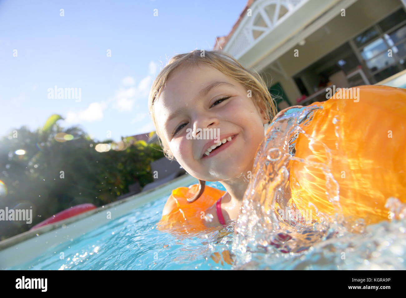 Cheerful 4-year-old girl playing in pool - Stock Image