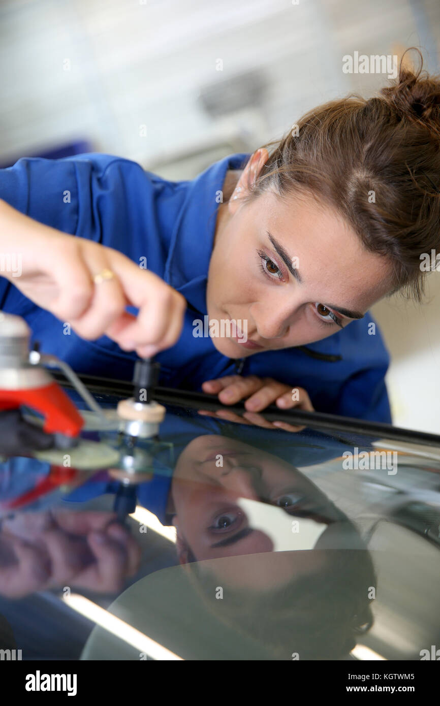 Young student in bodywork changing car windshield - Stock Image