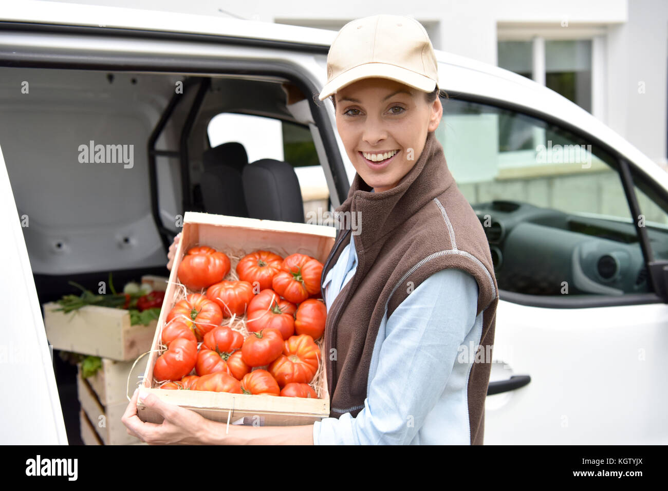 Cheerful farmer delivering fresh vegetables - Stock Image