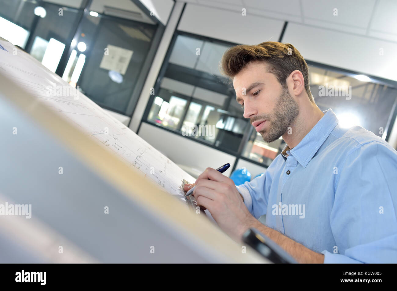 Architect designing on drafting table - Stock Image
