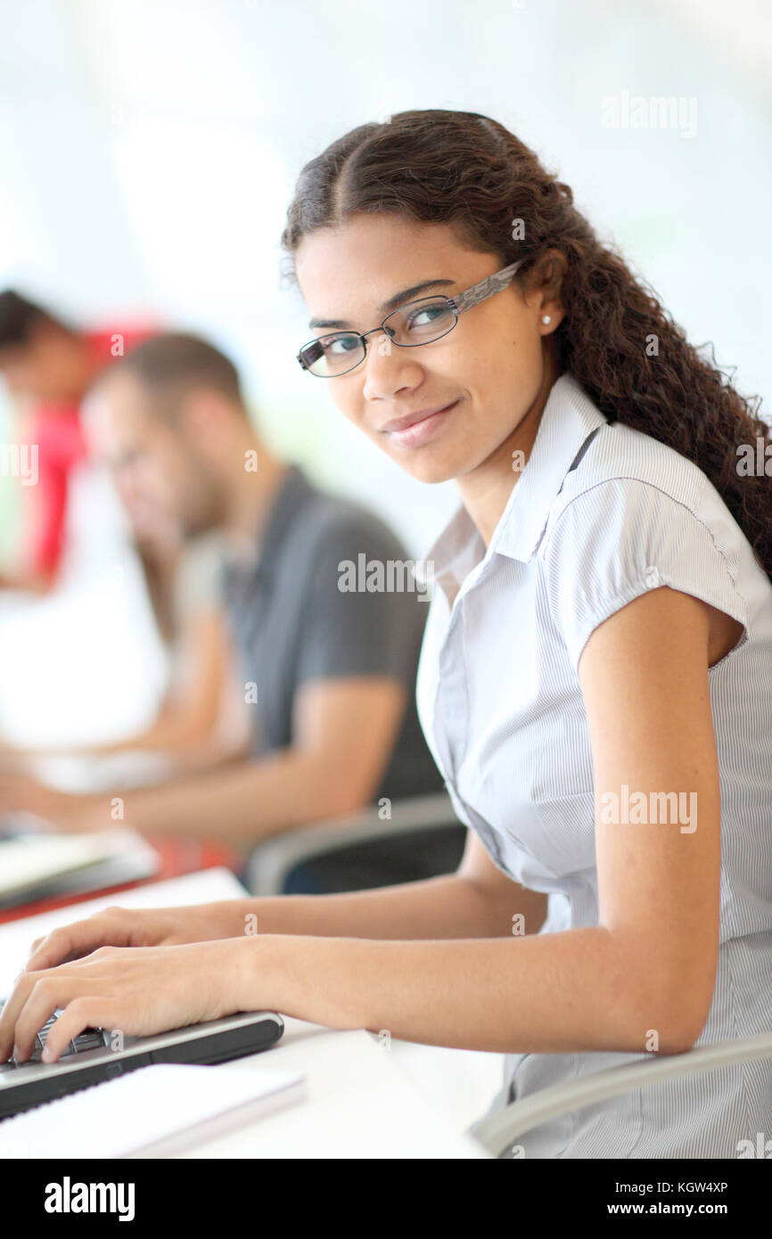 Portrait of smiling student in front of laptop computer - Stock Image