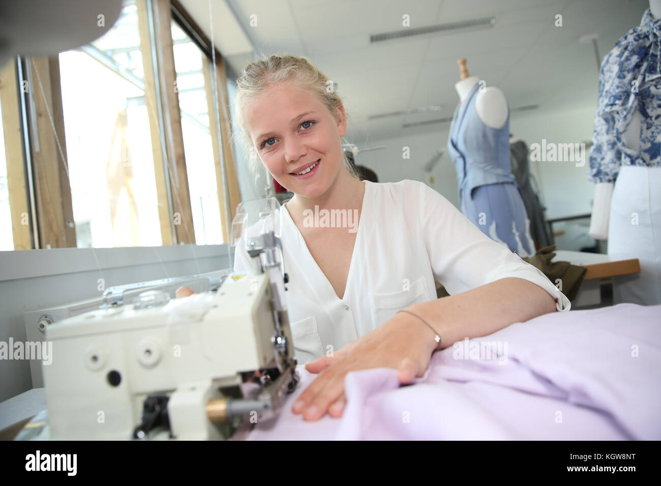 Young girl in sewing training course - Stock Image