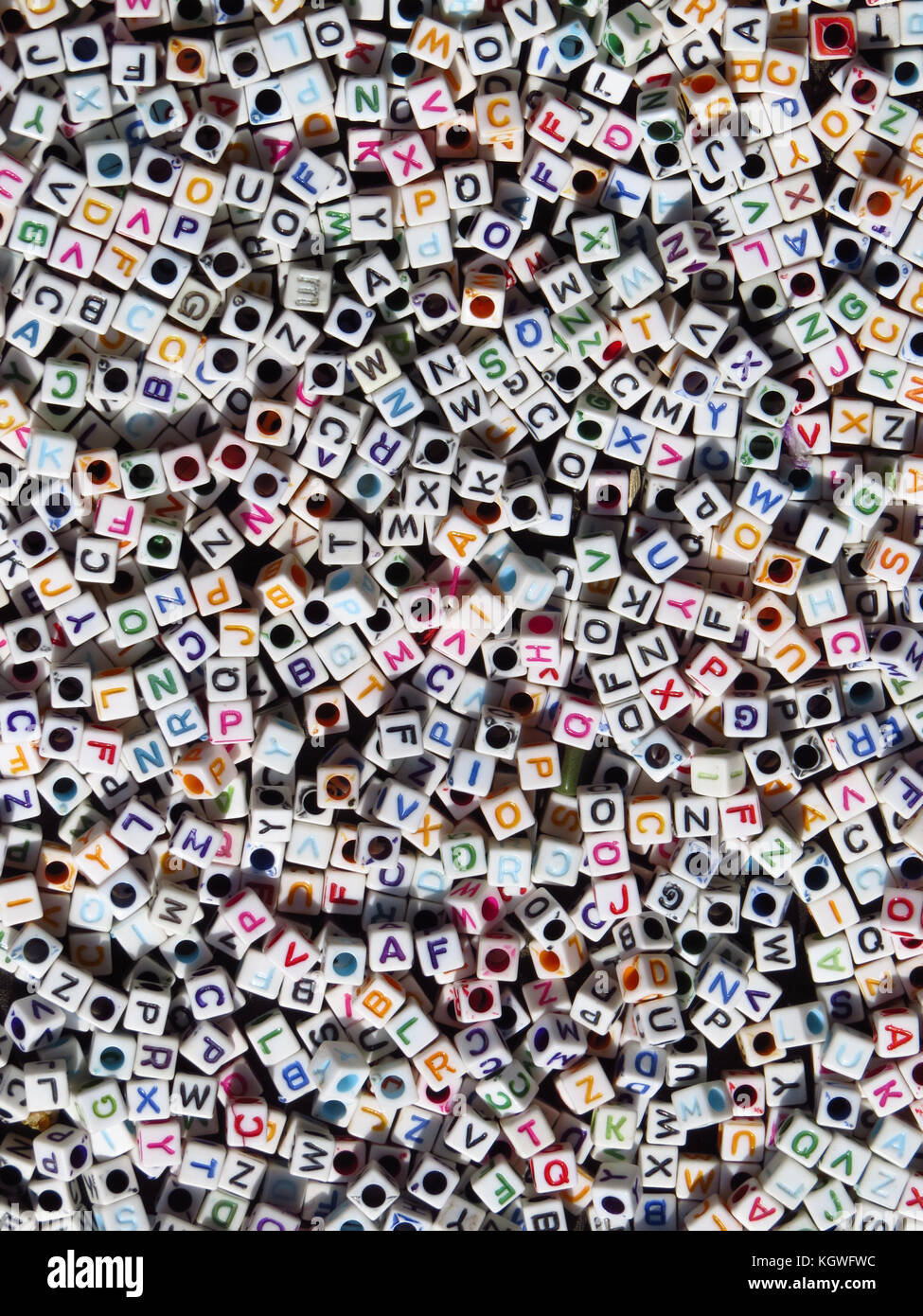 A background of beads of alphabets which are randomly arranged. - Stock Image