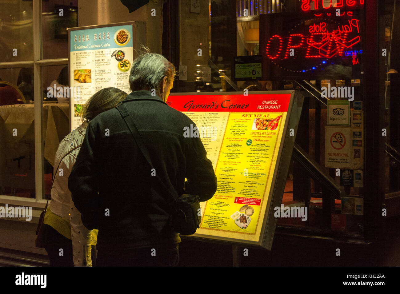Deciding what to eat from a menu outside a restaurant in China Town, London, England, UK. - Stock Image