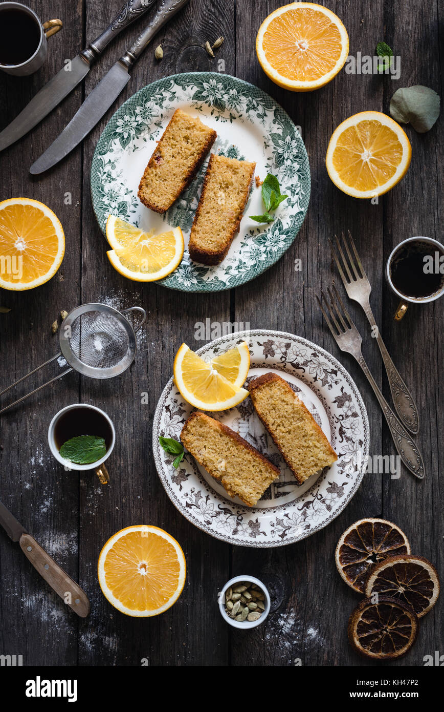 Orange cake served on vintage plate on rustic wooden table background. Food still life. Top view, vertical composition - Stock Image