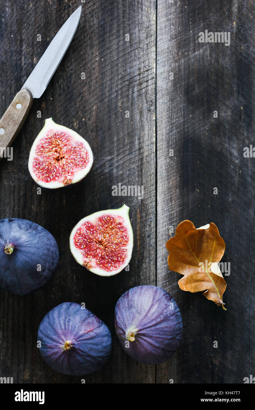 Fresh purple figs and table knife on old wooden background with copy space for text. Top view - Stock Image