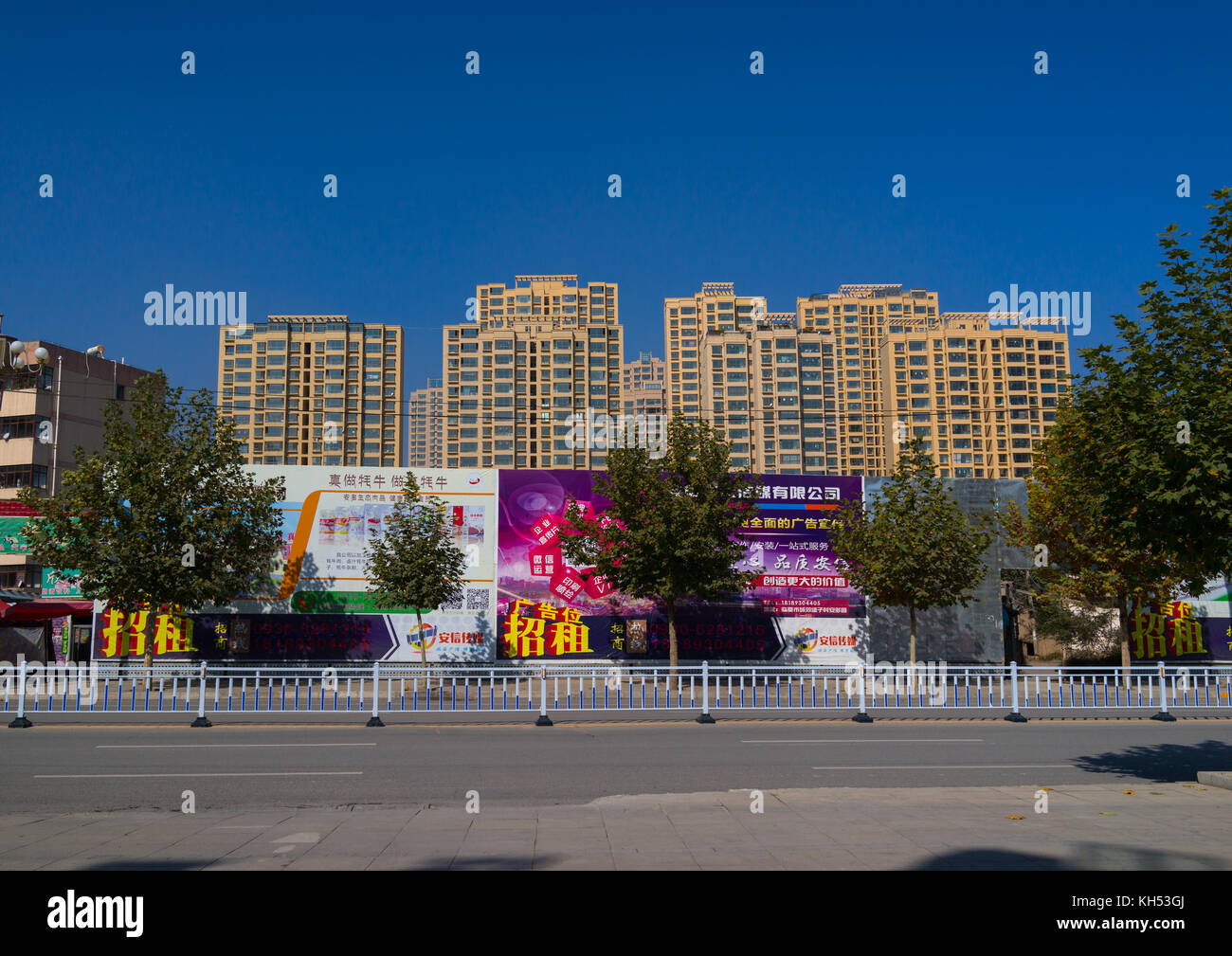Huge advertising billboards in front of new hirise buildings, Gansu province, Linxia, China - Stock Image