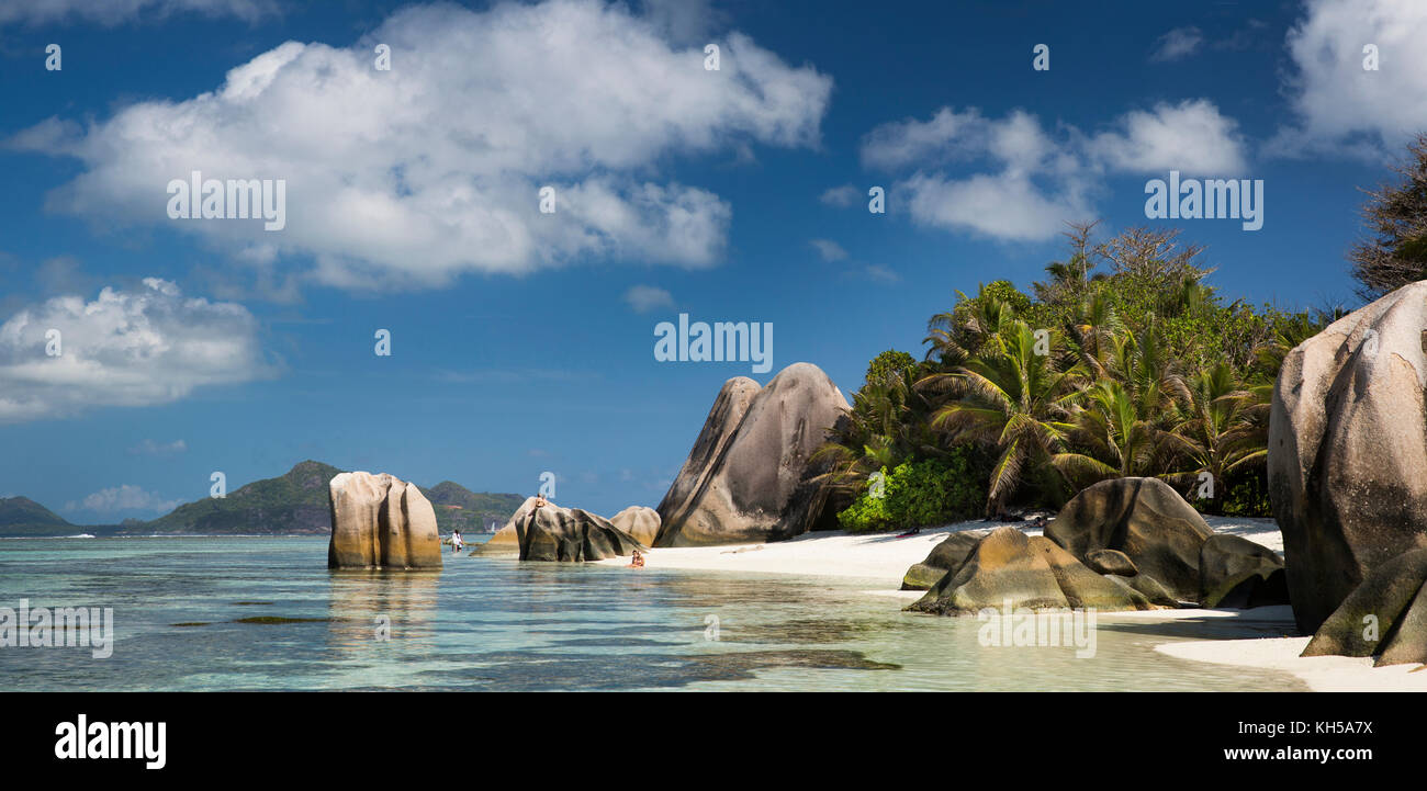 The Seychelles, La Digue, L'Union Estate, tourists in sea at Anse Source d'Argent beach, panoramic Stock Photo
