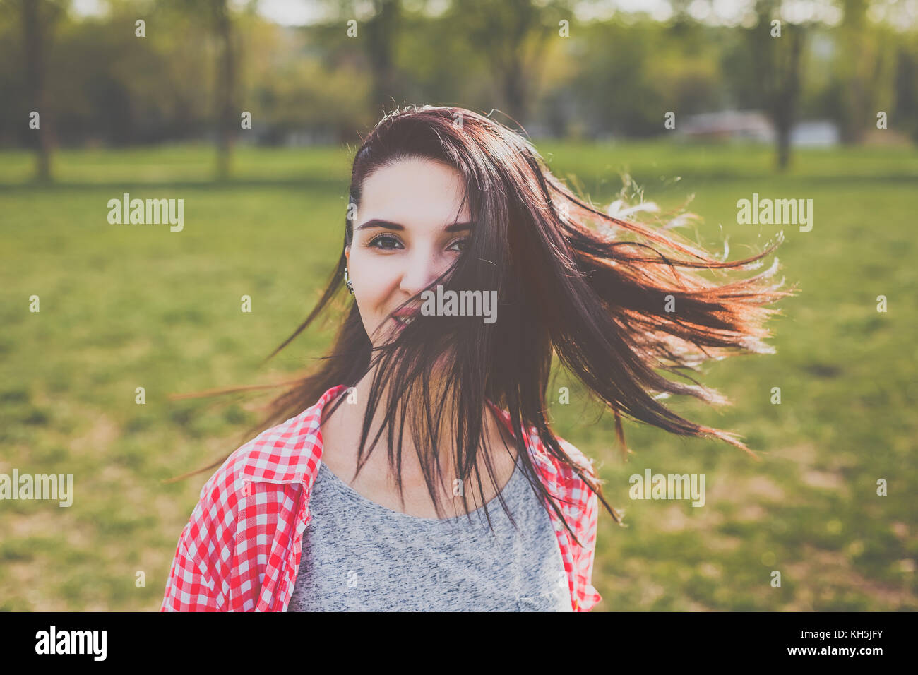 Attractive hipster girl smiling in wind - Stock Image