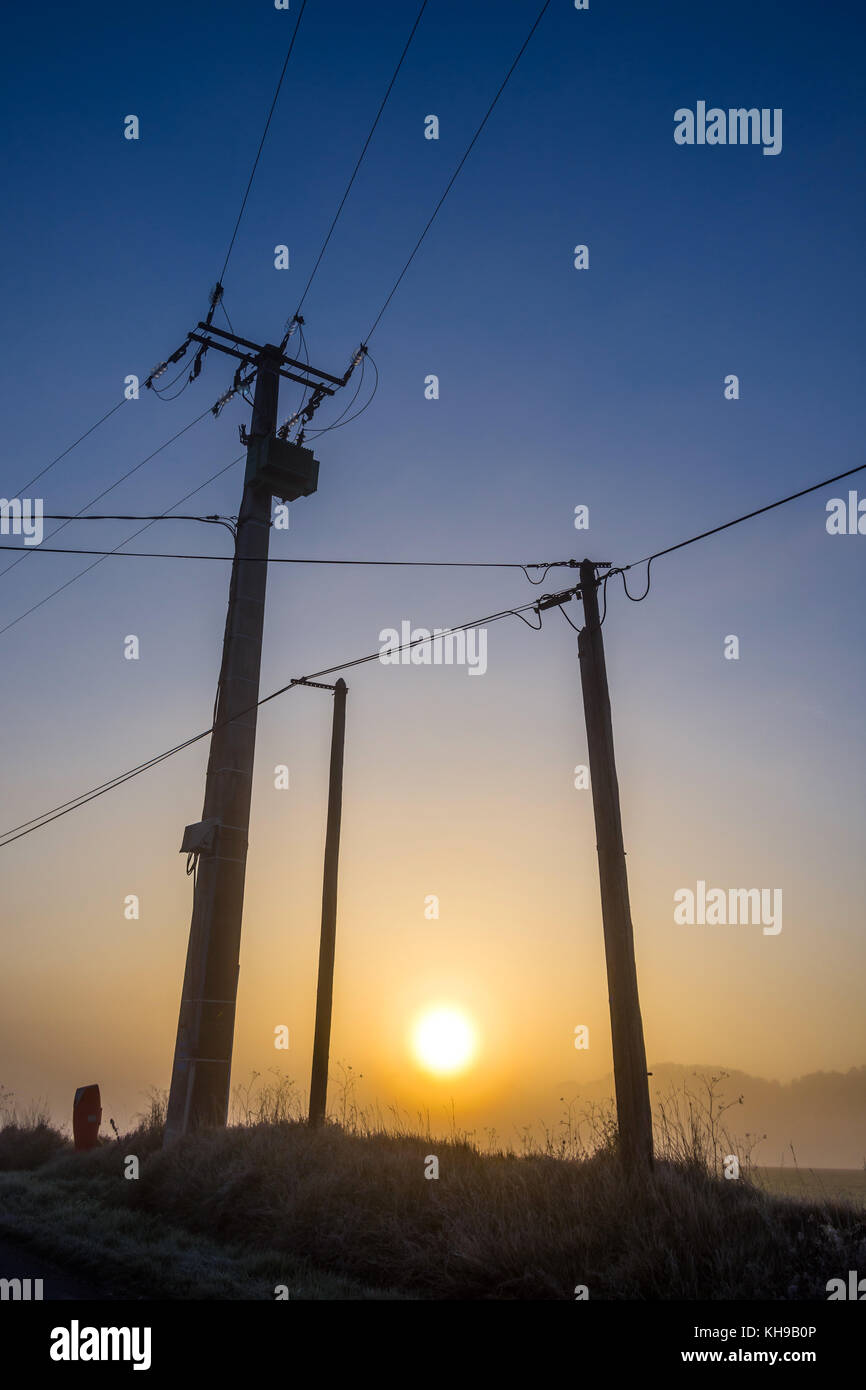 Misty sunrise silhouette between power poles and wires - France. - Stock Image