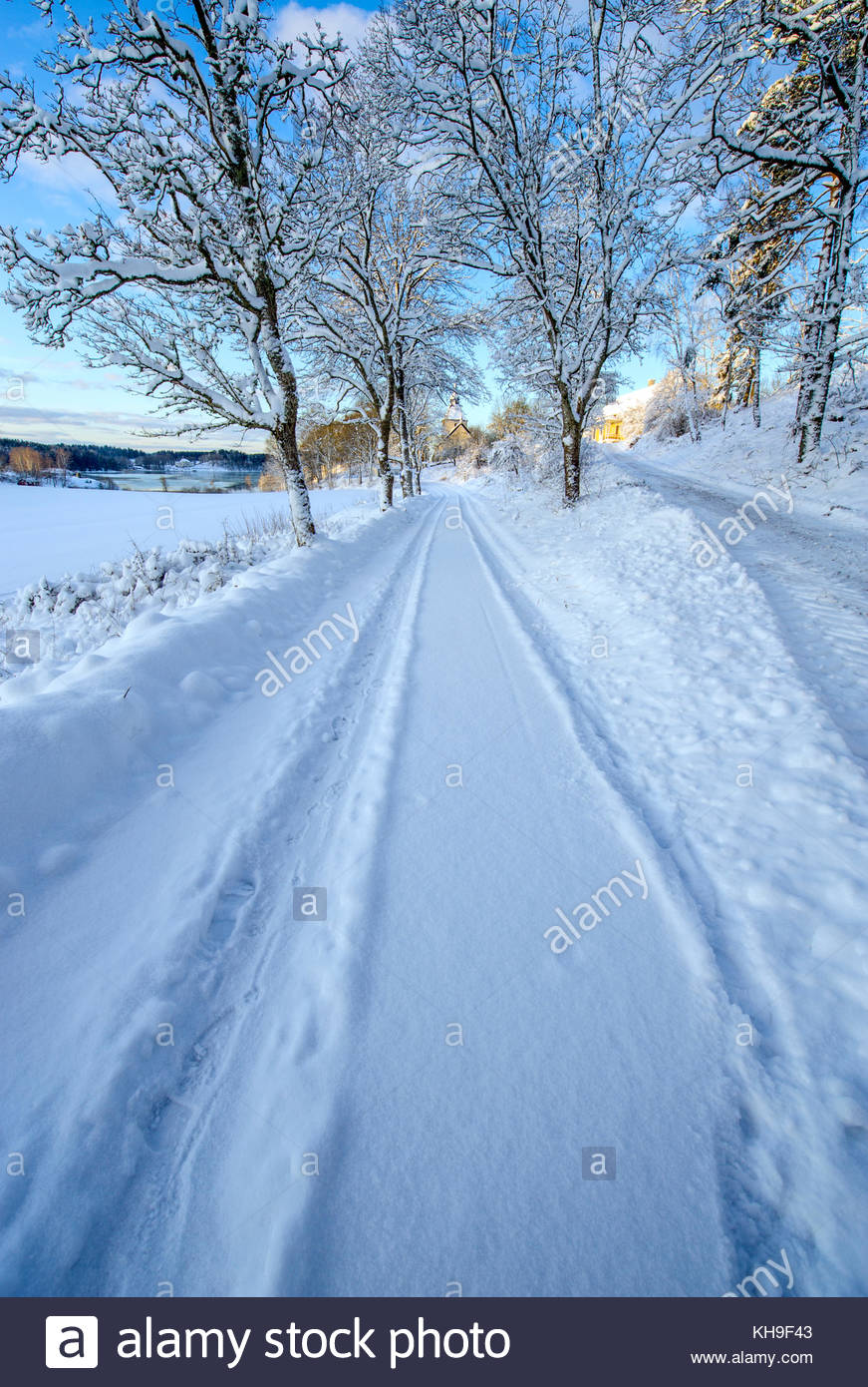 Winter road leading us into the photo. Heavy snow. - Stock Image