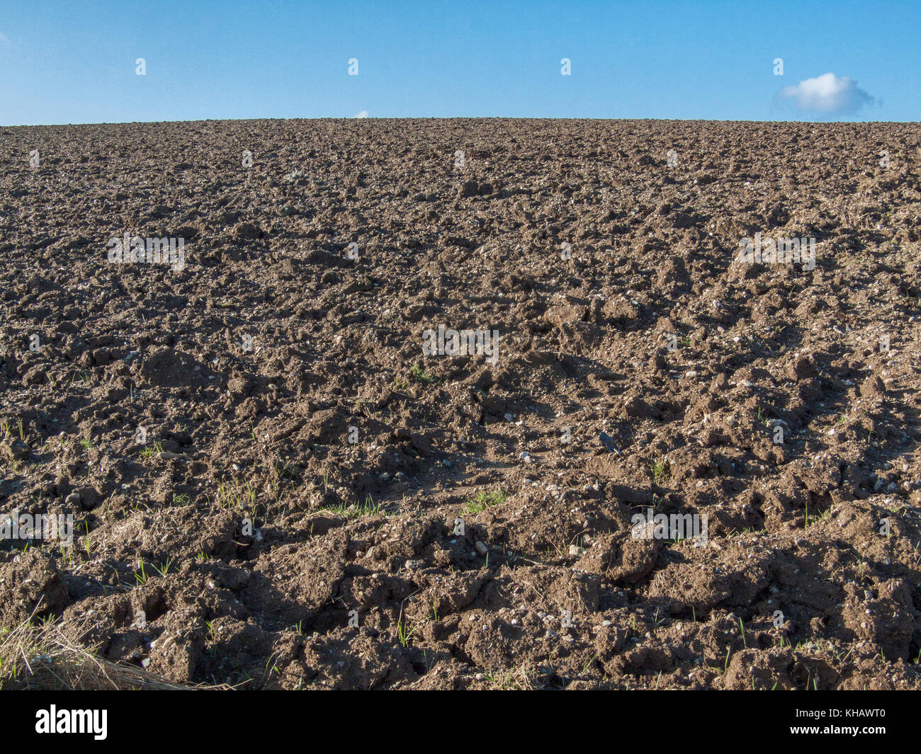 Sloping ploughed field against an autumnal blue sky. Metaphor for food security / growing food. - Stock Image