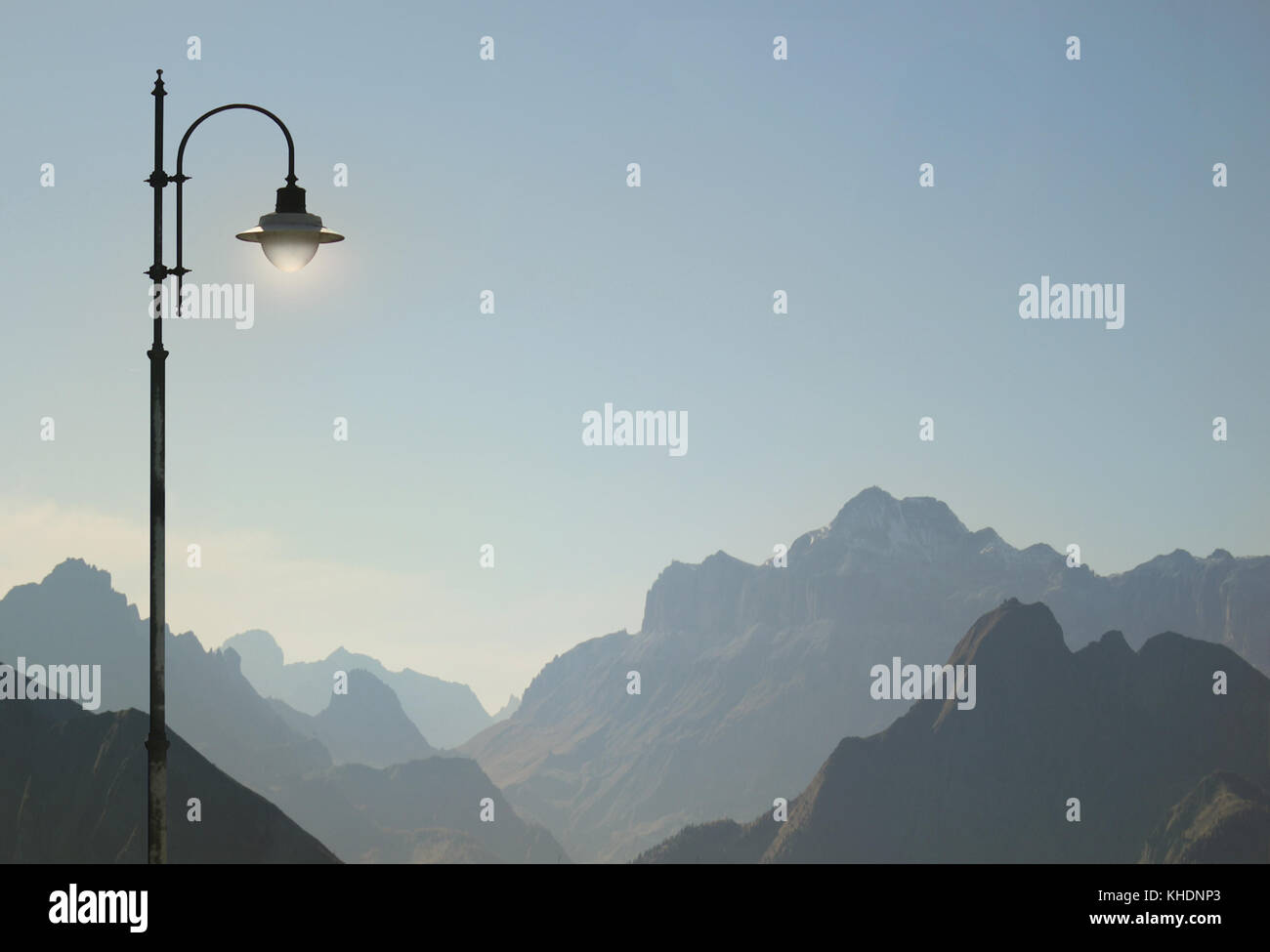 Beautiful and poetic view of Dolomites Alps in Italy with a street lamp detail - Stock Image