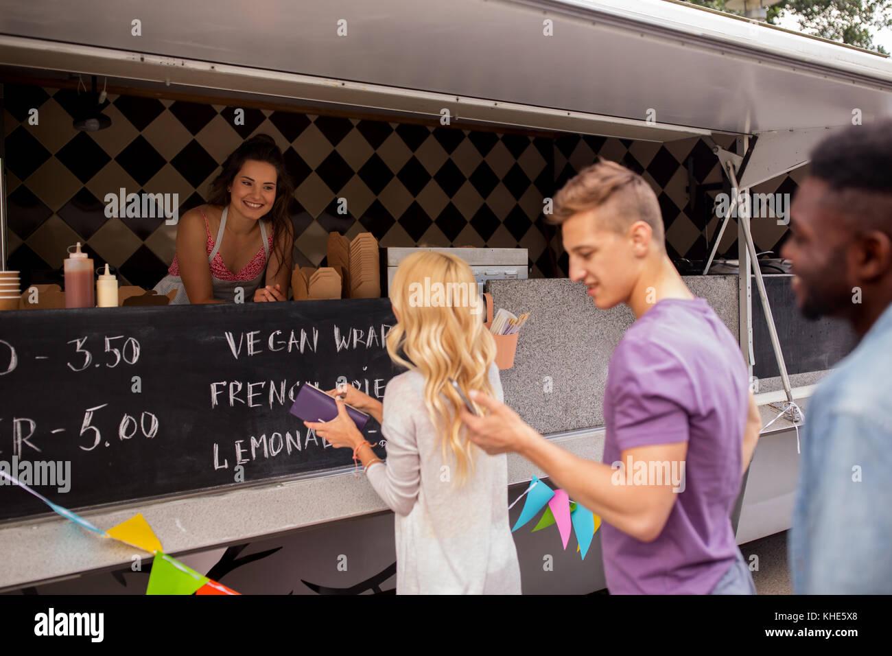 happy customers queue at food truck - Stock Image