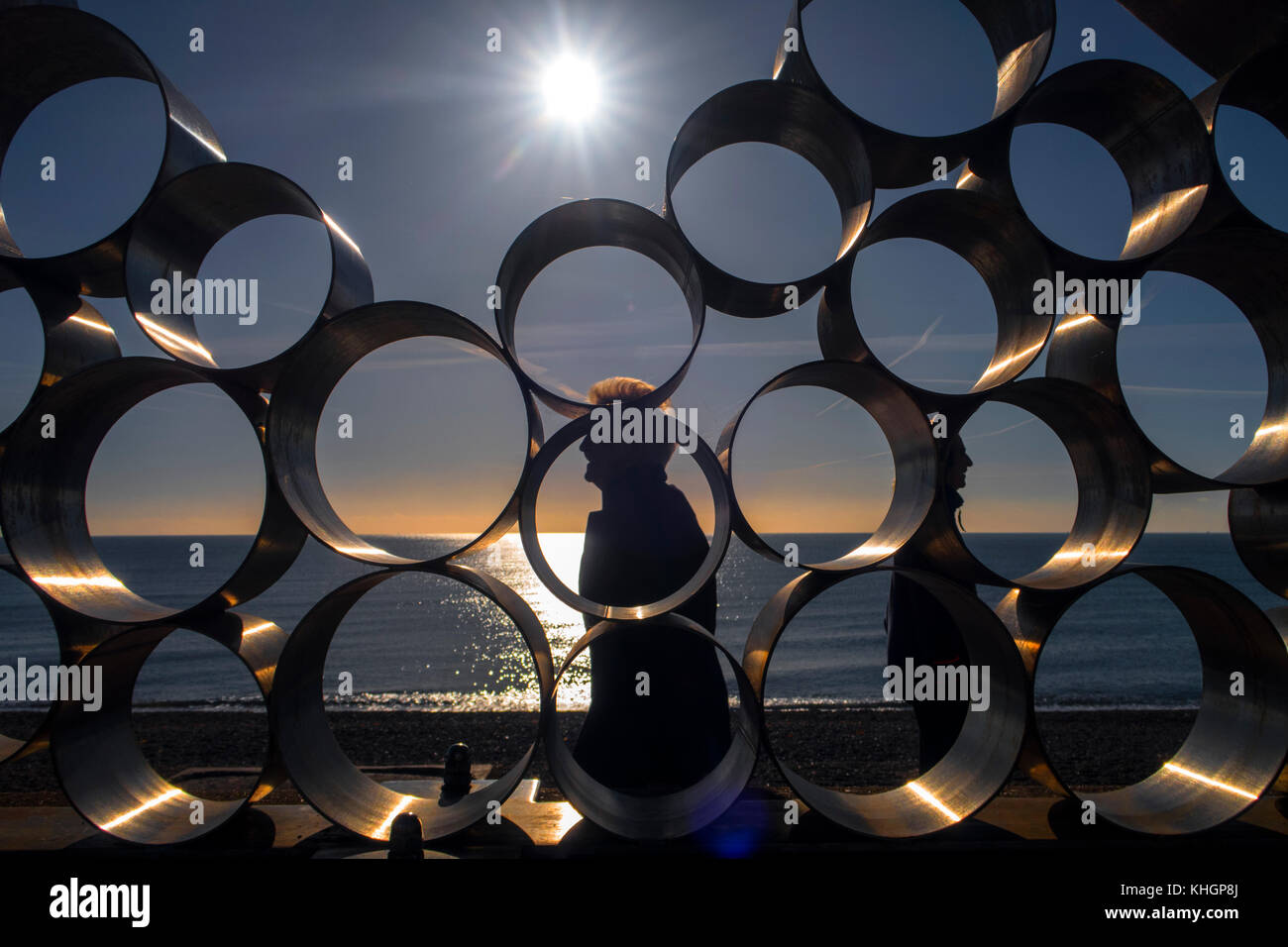 Seaton, Devon. 17th Nov, 2017. UK Weather. People walk past the Waves sculpture on the seafront at Seaton, Devon, Stock Photo
