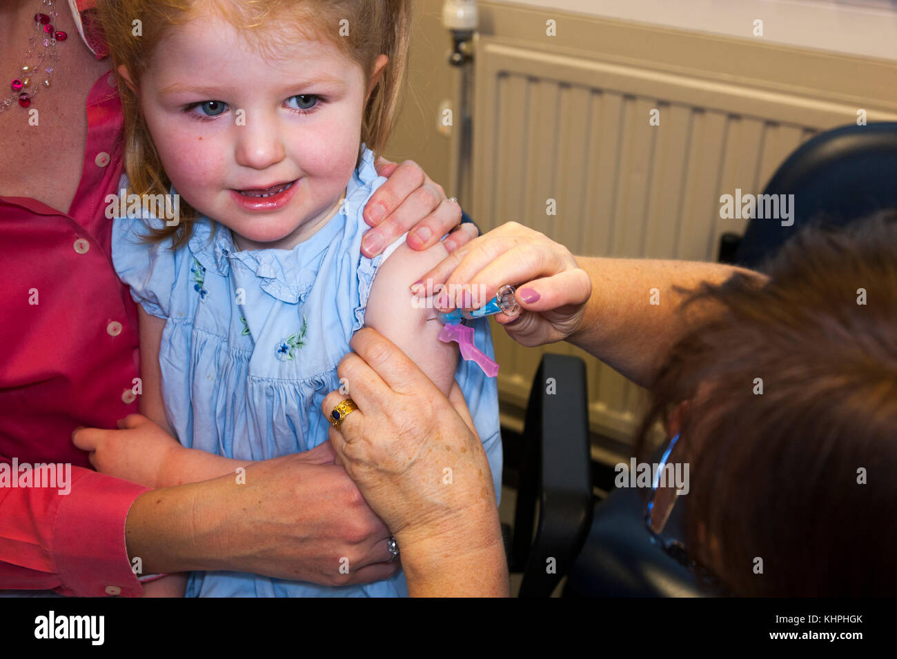 Practice nurse giving NHS 4-in-1 pre-school booster / Pre school booster & MMR second dose immunisation / inoculation Stock Photo