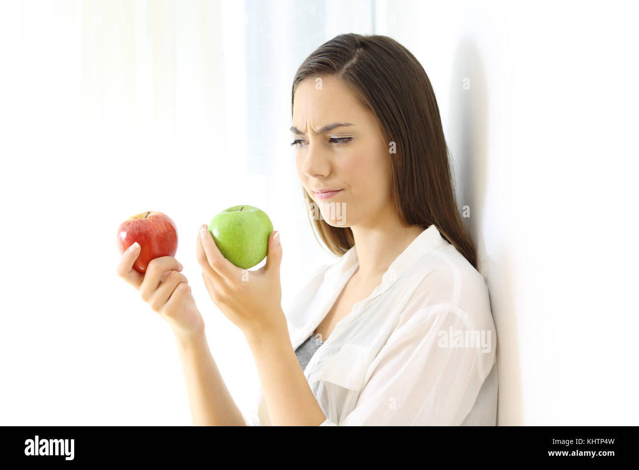 Doubtful woman deciding between red and green apples isolated on white at side - Stock Image